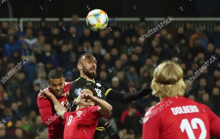 Kosovo's Vedat Muriqi, center top, jumps for the ball with Denmark's Mathias Jorgensen, top left, during a international friendly soccer match between Kosovo and Denmark at Fadil Vokrri stadium in Pristina, Kosovo
