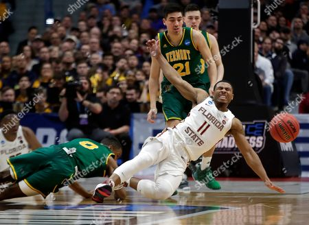 Stock Photo of David Nichols, Stef Smith, Everett Duncan. Florida State's David Nichols (11) reacts as he is fouled while chasing the ball against Vermont's Stef Smith (0) as Vermont's Everett Duncan (21) looks on during the second half of a first round men's college basketball game in the NCAA Tournament, in Hartford, Conn