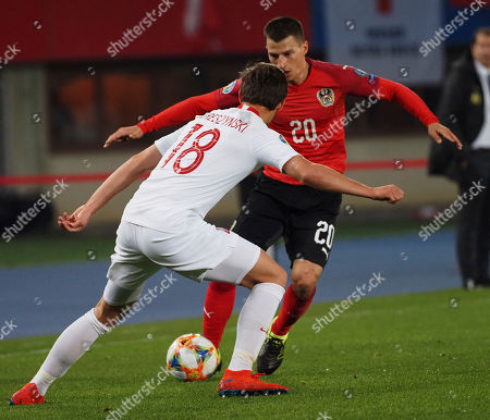 Austria's Stefan Lainer, right, fights for the ball with the Poland's Bartosz Bereszynski during the Euro 2020 group G qualifying soccer match between Austria and Poland at Ernst-Happel stadium in Vienna, Austria