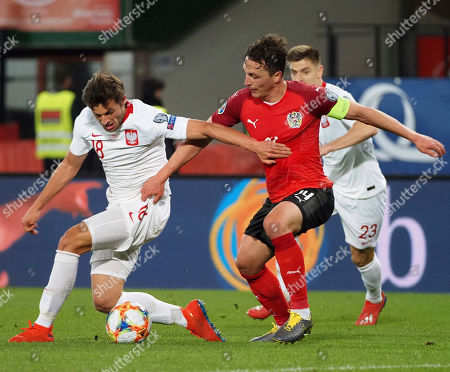 Austria's Julian Baumgartlinger, right, fights for the ball with the Poland's Bartosz Bereszynski, left, during the Euro 2020 group G qualifying soccer match between Austria and Poland at Ernst-Happel stadium in Vienna, Austria