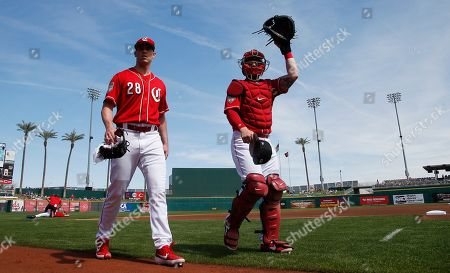 Stock Image of Cincinnati Reds starting pitcher Anthony DeSclafani (28) walks from the bullpen with catcher Tucker Barnhart, right, after warming up prior to a spring training baseball game against the Kansas City Royals, in Goodyear, Ariz