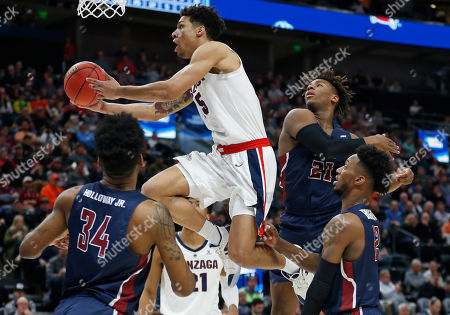 Alex Martin, Mike Holloway Jr., Elyjah Williams. Gonzaga guard Alex Martin (5) goes to the basket as Fairleigh Dickinson's Mike Holloway Jr. (34), Elyjah Williams (21) and Kaleb Bishop (12) defend during the second half of a first-round game in the NCAA men's college basketball tournament, in Salt Lake City