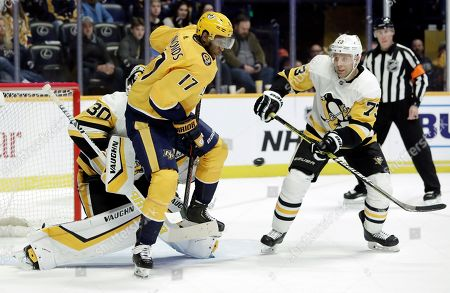 Wayne Simmonds, Jack Johnson. Nashville Predators forward Wayne Simmonds (17) jumps out of the way of a shot as Pittsburgh Penguins' Jack Johnson (73) defends during the second period of an NHL hockey game, in Nashville, Tenn