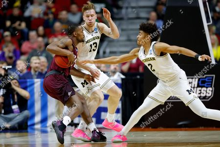 Montana guard Sayeed Pridgett, left, drives between Michigan's Ignas Brazdeikis (13) and Jordan Poole, right during a first round men's college basketball game in the NCAA Tournament, in Des Moines, Iowa