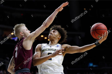 Michigan guard Jordan Poole shoots over Montana guard Timmy Falls, left, during a first round men's college basketball game in the NCAA Tournament, in Des Moines, Iowa