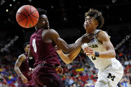 Michigan guard Jordan Poole looses the ball out of bounds in front of Montana guard Michael Oguine, left, during a first round men's college basketball game in the NCAA Tournament, in Des Moines, Iowa