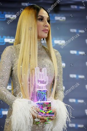 Puerto Rican singer Ivy Queen poses with her 'Trajectory' award during the ceremony of the Tu Musica Urbano Awards in San Juan, Puerto Rico, 21 March 2019. Puerto Rican singer Ozuna dominates the nominations with 19 awards and Daddy Yankee is recognized for his 25 year career as a leader of the musical movement.