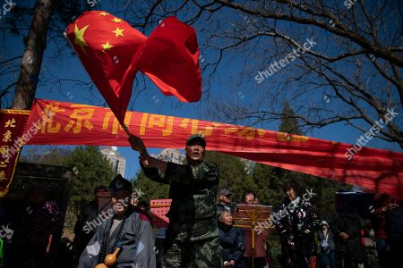 Stock Picture of A Chinese retiree waves the national flag besides a performer dressed as Ji Gong, a Buddhist monk from the Song dynasty, during a community performance in a park in Beijing, China, 22 March 2019. Chinese residents, especially retirees, elderly people and children are out in the parks enjoying the warmer weather and sunshine as spring descends on Beijing.