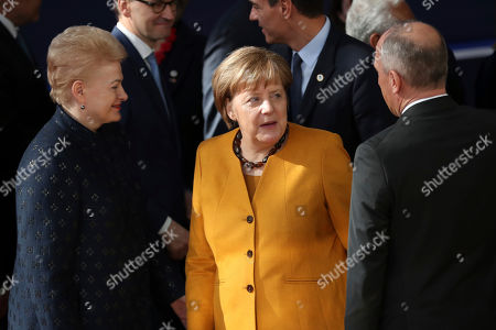 German Chancellor Angela Merkel, center, speaks with Lithuanian President Dalia Grybauskaite, left, and Leichtenstein's Prime Minister Adrian Hasler during a group photo at an EU summit in Brussels, . European Union leaders gathered again Friday after deciding that the political crisis in Britain over Brexit poses too great a threat and that action is needed to protect the smooth running of the world's biggest trading bloc