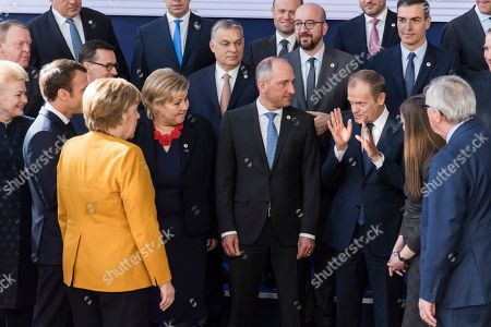 European Council President Donald Tusk, third right, speaks with Leichtenstein's Prime Minister Adrian Hasler, center right, and Norway's Prime Minister Erna Solberg, center left, during a group photo at an EU summit in Brussels, . European Union leaders gathered again Friday after deciding that the political crisis in Britain over Brexit poses too great a threat and that action is needed to protect the smooth running of the world's biggest trading bloc