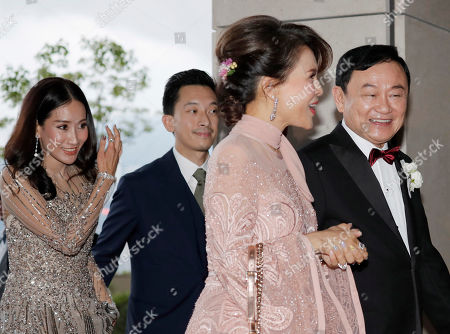 "Stock Photo of Thaksin Shinawatra, Ubolratana, Nattapong ""Pong"" Kunakornwong, Aim Pintongtha. Former Thai Prime Minister Thaksin Shinawatra, right, walks with Princess Ubolratana of Thailand, and followed by his daughter Pintongtha ""Aim"", left, and her husband Nattapong ""Pong"" Kunakornwong as they arrive at the wedding of Thaksin's youngest daughter Paetongtarn ""Ing"" Shinawatra at a hotel in Hong Kong"