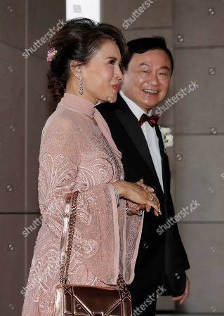 """Stock Photo of Thaksin Shinawatra, Ubolratana, Nattapong. Former Thai Prime Minister Thaksin Shinawatra, right, walks with Princess Ubolratana of Thailand as they arrive the wedding of his youngest daughter Paetongtarn """"Ing"""" Shinawatra at a hotel in Hong Kong"""