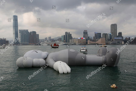 The 'KAWS:HOLIDAY' 'Companion', is docked at the waterfront of the Victoria Harbour after the opening ceremony for its exhibition in Hong Kong, . The 37-meter long 'KAWS:HOLIDAY' 'Companion', is an inflatable sculpture created by US artist and designer Brian Donnelly, known professionally as Kaws
