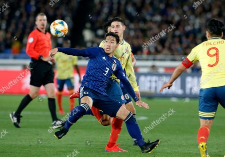 Japan's Gen Shoji, center, eyes on the ball during a friendly soccer match between Japan and Colombia in Yokohama, Japan