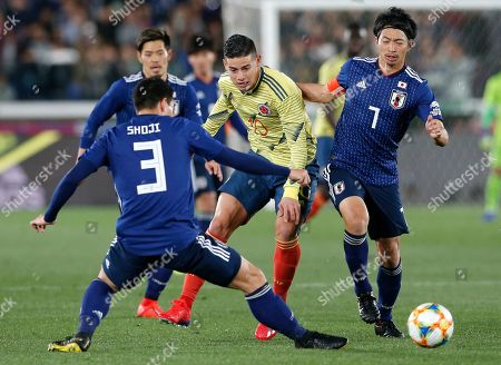 Colombia's James Rodriguez, center, is surrounded by Japan's Gaku Shibasaki, right, and Gen Shoji during a friendly soccer match between Japan and Colombia in Yokohama, Japan