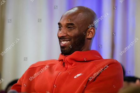 Former Los Angeles Lakers NBA basketball player Kobe Bryant listens to a question as he meets with students at Andrew Hamilton School in Philadelphia, . Kobe Bryant was promoting the book The Wizenard Series: Training Camp he created with writer Wesley King