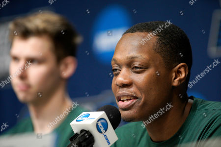Michigan State's Cassius Winston speaks during a news conference in Des Moines, Iowa, ahead of their second round men's college basketball game against Minnesota in the NCAA Tournament, with Matt McQuaid, left
