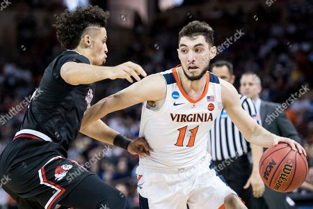 Virginia guard Ty Jerome (11) dribbles the ball against Gardner-Webb guard Jose Perez, left, during a first-round game in the NCAA men's college basketball tournament, in Columbia, S.C