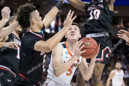 Virginia guard Kyle Guy (5) attempts a shot against Gardner-Webb guard Jose Perez (5) during a first-round game in the NCAA men's college basketball tournament, in Columbia, S.C. Virginia defeated Gardner-Webb 71-56