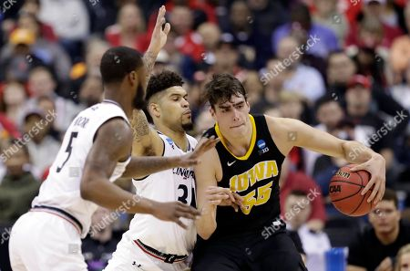Iowa's Luka Garza (55) drives past Cincinnati's Jarron Cumberland (34) and Trevor Moore (5) in the second half during a first round men's college basketball game in the NCAA Tournament in Columbus, Ohio