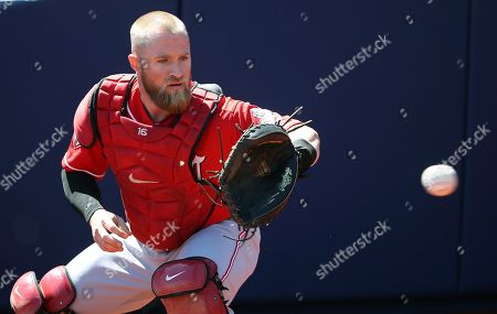 Cincinnati Reds catcher Tucker Barnhart warms up prior to a spring training baseball game against the Milwaukee Brewers, in Phoenix
