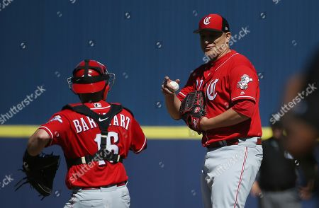 Cincinnati Reds relief pitcher David Hernandez, right, talks with Reds catcher Tucker Barnhart, left, during the fourth inning of a spring training baseball game against the Milwaukee Brewers, in Phoenix