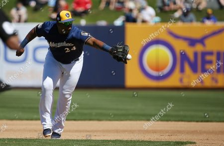Milwaukee Brewers first baseman Jesus Aguilar flips the ball to first base for the out on Cincinnati Reds' Tucker Barnhart during the fourth inning of a spring training baseball game, in Phoenix