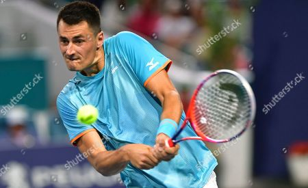 Bernard Tomic, of Australia, hits a shot from Novak Djokovic, of Serbia, during the Miami Open tennis tournament, in Miami Gardens, Fla
