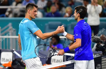 Novak Djokovic, right, of Serbia, shakes hands with Bernard Tomic, of Australia, following their match at the Miami Open tennis tournament, in Miami Gardens, Fla