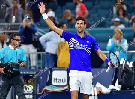 Novak Djokovic, of Serbia, waves to the crowd after his win over Bernard Tomic, of Australia, during the Miami Open tennis tournament, in Miami Gardens, Fla