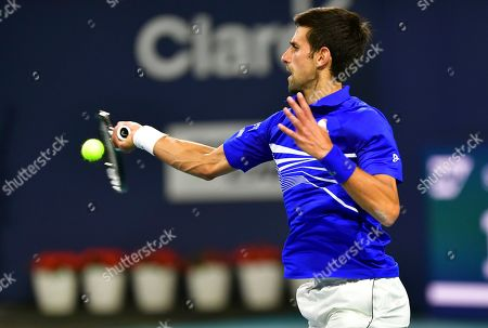 Novak Djokovic, of Serbia, hits a forehand to Bernard Tomic, of Australia, during the Miami Open tennis tournament, in Miami Gardens, Fla