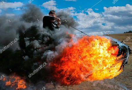 On, a young man spins a burning tire on a metal chain during a ritual marking the upcoming Clean Monday, the beginning of the Great Lent, 40 days ahead of Orthodox Easter, on the hills surrounding the village of Poplaca, in central Romania's Transylvania region. Romanian villagers burn piles of used tires then spin them in the Transylvanian hills in a ritual they believe will ward off evil spirits as they begin a period of 40 days of abstention, when Orthodox Christians cut out meat, fish, eggs, and dairy