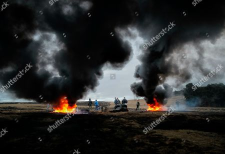 In this picture taken, a children and youngsters stand by burning tires during a ritual marking the upcoming Clean Monday, the beginning of the Great Lent, 40 days ahead of Orthodox Easter, on the hills surrounding the village of Poplaca, in central Romania's Transylvania region. Romanian villagers burn piles of used tires then spin them in the Transylvanian hills in a ritual they believe will ward off evil spirits as they begin a period of 40 days of abstention, when Orthodox Christians cut out meat, fish, eggs, and dairy