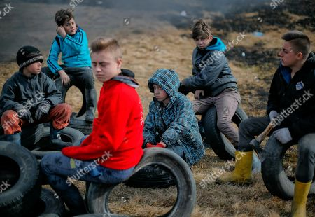 On, a children sit on tires during a ritual marking the upcoming Clean Monday, the beginning of the Great Lent, 40 days ahead of Orthodox Easter, on the hills surrounding the village of Poplaca, in central Romania's Transylvania region. Romanian villagers burn piles of used tires then spin them in the Transylvanian hills in a ritual they believe will ward off evil spirits as they begin a period of 40 days of abstention, when Orthodox Christians cut out meat, fish, eggs, and dairy