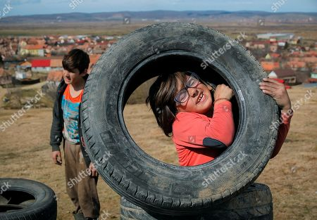 On, a little girl struggles to lift a tire during a ritual marking the upcoming Clean Monday, the beginning of the Great Lent, 40 days ahead of Orthodox Easter, on the hills surrounding the village of Poplaca, in central Romania's Transylvania region. Romanian villagers burn piles of used tires then spin them in the Transylvanian hills in a ritual they believe will ward off evil spirits as they begin a period of 40 days of abstention, when Orthodox Christians cut out meat, fish, eggs, and dairy