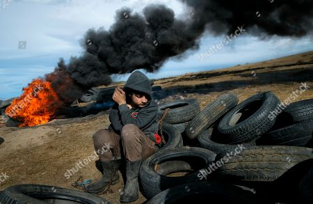 On, a boy pauses during a ritual marking the upcoming Clean Monday, the beginning of the Great Lent, 40 days ahead of Orthodox Easter, on the hills surrounding the village of Poplaca, in central Romania's Transylvania region. Romanian villagers burn piles of used tires then spin them in the Transylvanian hills in a ritual they believe will ward off evil spirits as they begin a period of 40 days of abstention, when Orthodox Christians cut out meat, fish, eggs, and dairy
