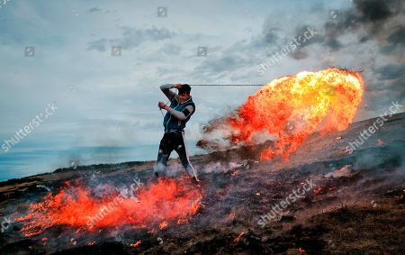 In this picture taken, a young man spins a burning tire on a metal chain during a ritual marking the upcoming Clean Monday, the beginning of the Great Lent, 40 days ahead of Orthodox Easter, on the hills surrounding the village of Poplaca, in central Romania's Transylvania region. Romanian villagers burn piles of used tires then spin them in the Transylvanian hills in a ritual they believe will ward off evil spirits as they begin a period of 40 days of abstention, when Orthodox Christians cut out meat, fish, eggs, and dairy