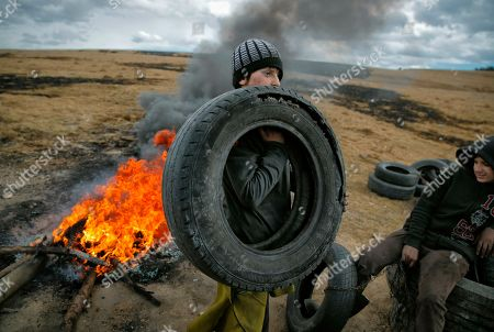 Stock Image of On, a boy holds a tire, during a ritual marking the upcoming Clean Monday, the beginning of the Great Lent, 40 days ahead of Orthodox Easter, on the hills surrounding the village of Poplaca, in central Romania's Transylvania region. Romanian villagers burn piles of used tires then spin them in the Transylvanian hills in a ritual they believe will ward off evil spirits as they begin a period of 40 days of abstention, when Orthodox Christians cut out meat, fish, eggs, and dairy