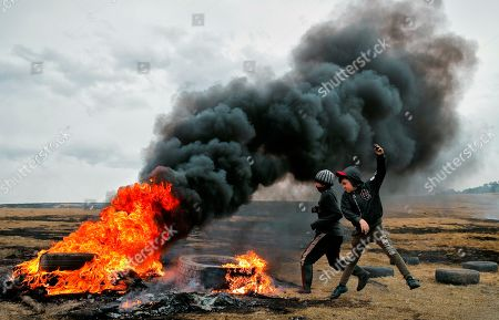 Stock Photo of In this picture taken, children jump after pushing a burning tire during a ritual marking the upcoming Clean Monday, the beginning of the Great Lent, 40 days ahead of Orthodox Easter, on the hills surrounding the village of Poplaca, in central Romania's Transylvania region. Romanian villagers burn piles of used tires then spin them in the Transylvanian hills in a ritual they believe will ward off evil spirits as they begin a period of 40 days of abstention, when Orthodox Christians cut out meat, fish, eggs, and dairy