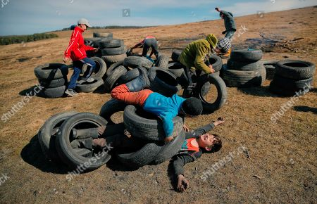 Stock Picture of On, children play with used tires before a ritual marking the upcoming Clean Monday, the beginning of the Great Lent, 40 days ahead of Orthodox Easter, on the hills surrounding the village of Poplaca, in central Romania's Transylvania region. Romanian villagers burn piles of used tires then spin them in the Transylvanian hills in a ritual they believe will ward off evil spirits as they begin a period of 40 days of abstention, when Orthodox Christians cut out meat, fish, eggs, and dairy