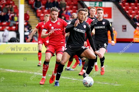 Barnsley forward Jacob Brown (33) beats Walsall FC defender Luke Leahy (3) to the ball during the EFL Sky Bet League 1 match between Walsall and Barnsley at the Banks's Stadium, Walsall
