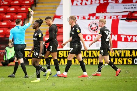 Referee Ben Toner shows Barnsley forward Jacob Brown (33) the yellow card for taking his shirt off after scoring the winning goal in time added on during the EFL Sky Bet League 1 match between Walsall and Barnsley at the Banks's Stadium, Walsall