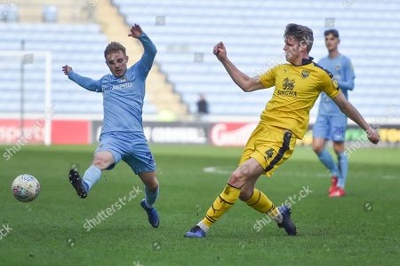 Oxford United defender Rob Dickie (4) clears the ball under pressure from Coventry City midfielder (on loan from Derby County Luke Thomas (23) during the EFL Sky Bet League 1 match between Coventry City and Oxford United at the Ricoh Arena, Coventry