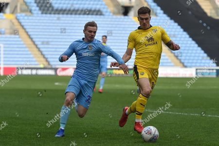 Oxford United midfielder Josh Ruffels (14) battles for possession  with Coventry City midfielder (on loan from Derby County Luke Thomas (23) during the EFL Sky Bet League 1 match between Coventry City and Oxford United at the Ricoh Arena, Coventry
