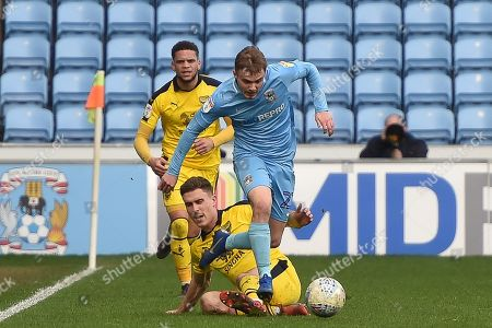Coventry City midfielder (on loan from Derby County Luke Thomas (23) skips the tackle of Oxford United midfielder Josh Ruffels (14) during the EFL Sky Bet League 1 match between Coventry City and Oxford United at the Ricoh Arena, Coventry