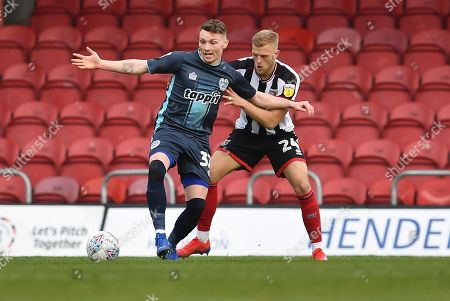 Grimsby Town defender Harry Davis(24) and Bury FC forward Caolan Lavery (32)  during the EFL Sky Bet League 2 match between Grimsby Town FC and Bury at Blundell Park, Grimsby