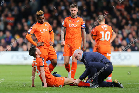 Dan Potts of Luton Town receives treatments to his knee