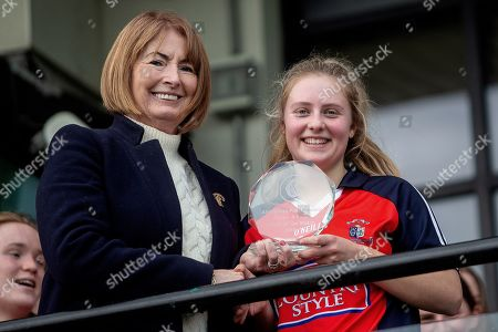 St. Angela's Ursuline vs Cross & Passion. St. Angela's Ursuline's Annie Fitzgerald receives the Player of the Match award from Kathleen Woods, President of The Camogie Association