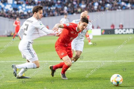 Geogia's Otar Kakabadze (L) fights for the ball against Switzerland's Steven Zuber (R) during the UEFA Euro 2020 qualifier Group D soccer match between Georgia and Switzerland at the Dinamo Arena in Tbilisi, Georgia, 23 March 2019.