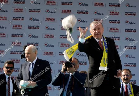 Recep Tayyip Erdogan, Devlet Bahceli. Turkey's President Recep Tayyip Erdogan, right, and Devlet Bahceli, left, the leader of opposition Nationalist Movement Party, MHP, throw bags containing tea towards the supporters of MHP and ruling Justice and Development Party, AKP, during a joint rally in Ankara, Turkey, . Erdogan's AKP and MHP made an alliance for the countrywide local elections scheduled for March 31, 2019 with 57 million registered voters